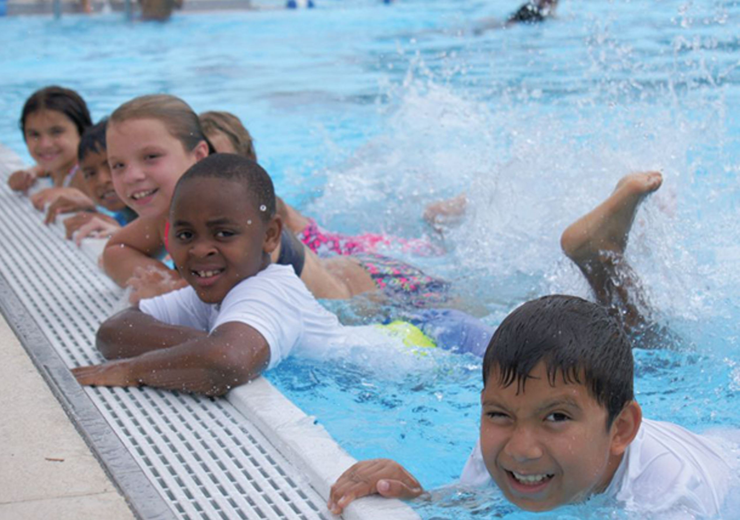 Students holding wall during swim lessons kicking water