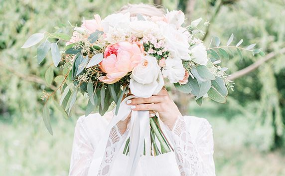 picture of bride holding flowers in front of face