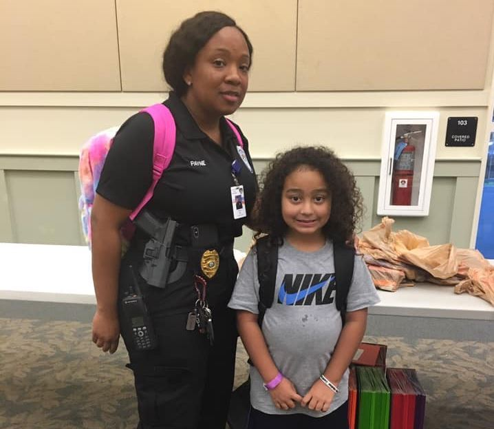 Sgt. Tishelle Payne poses with a youngster for a Back 2 School Bash in August 2019.